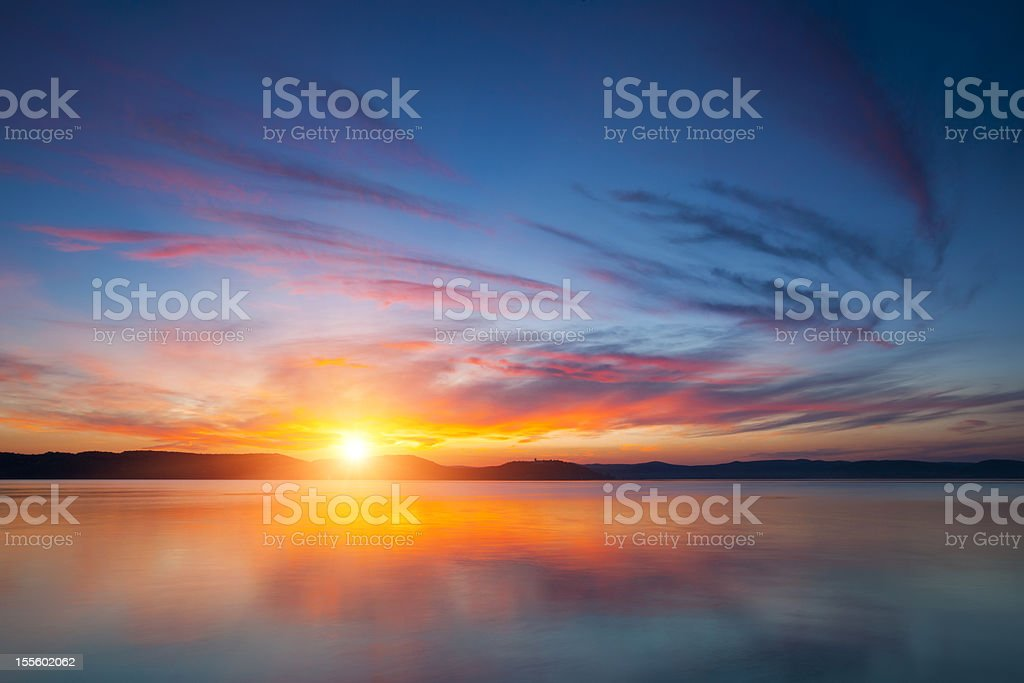 A stunning view of the sunset over water stock photo