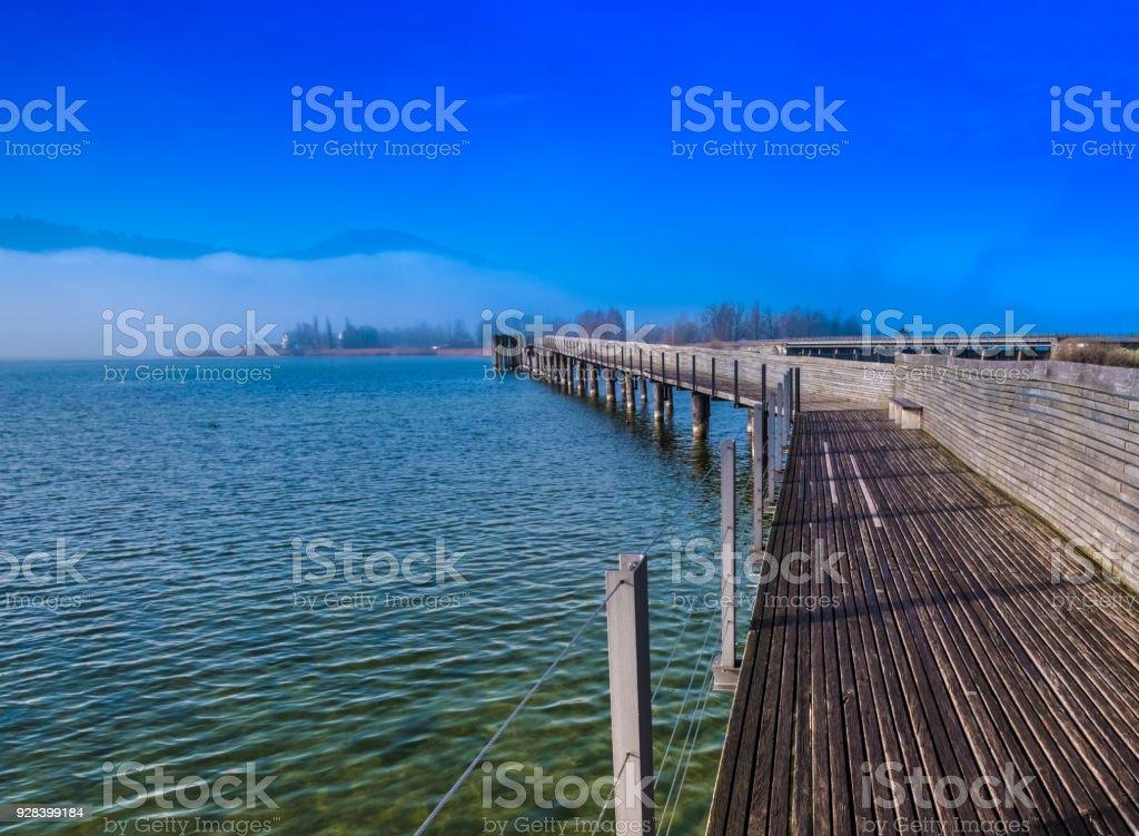 Stunning views of the Holzsteg, a wooden footbridge crossing the Upper Zurich Lake and part of the old Way of Saint James (Jakobsweg, Camino de Santiago) between Rapperswil and Hurden, Sankt Gallen, Schwyz, Switzerland stock photo