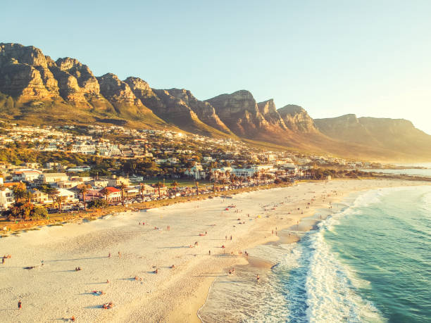 stunning wide angle aerial drone evening view of camps bay, an affluent suburb of cape town, western cape, south africa. twelve apostles mountain range in the background. photo cross processed. - table mountain national park stock pictures, royalty-free photos & images