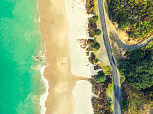 Stunning wide angle aerial drone view of Otama Beach and Black Jack Road near Matarangi on the Coromandel Peninsula in New Zealand. Beautiful pattern / texture of ocean, beach, trees and the road.