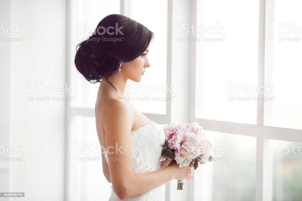 Stunning young bride holding bouquet stock photo