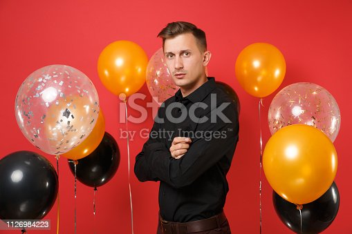 istock Stunning young man in black classic shirt celebrating holding hands folded on red background air balloons. Valentine's, International Women's Day, Happy New Year birthday mockup holiday party concept. 1126984223