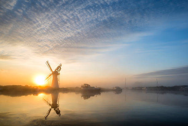 Stunnnig landscape of windmill and river at dawn stock photo