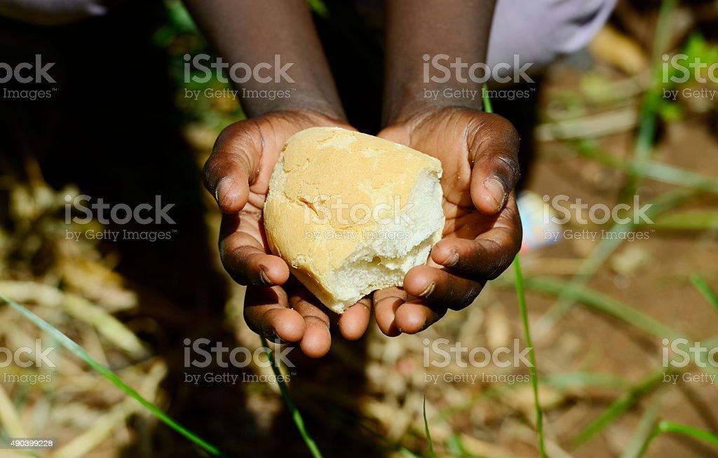 Stunting African Children Symbol - Baby Girl Holding Bread Malnutrition stock photo