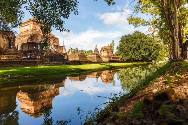 stupas e rio no parque histórico de sukhothai, tailândia - sukhothai - fotografias e filmes do acervo
