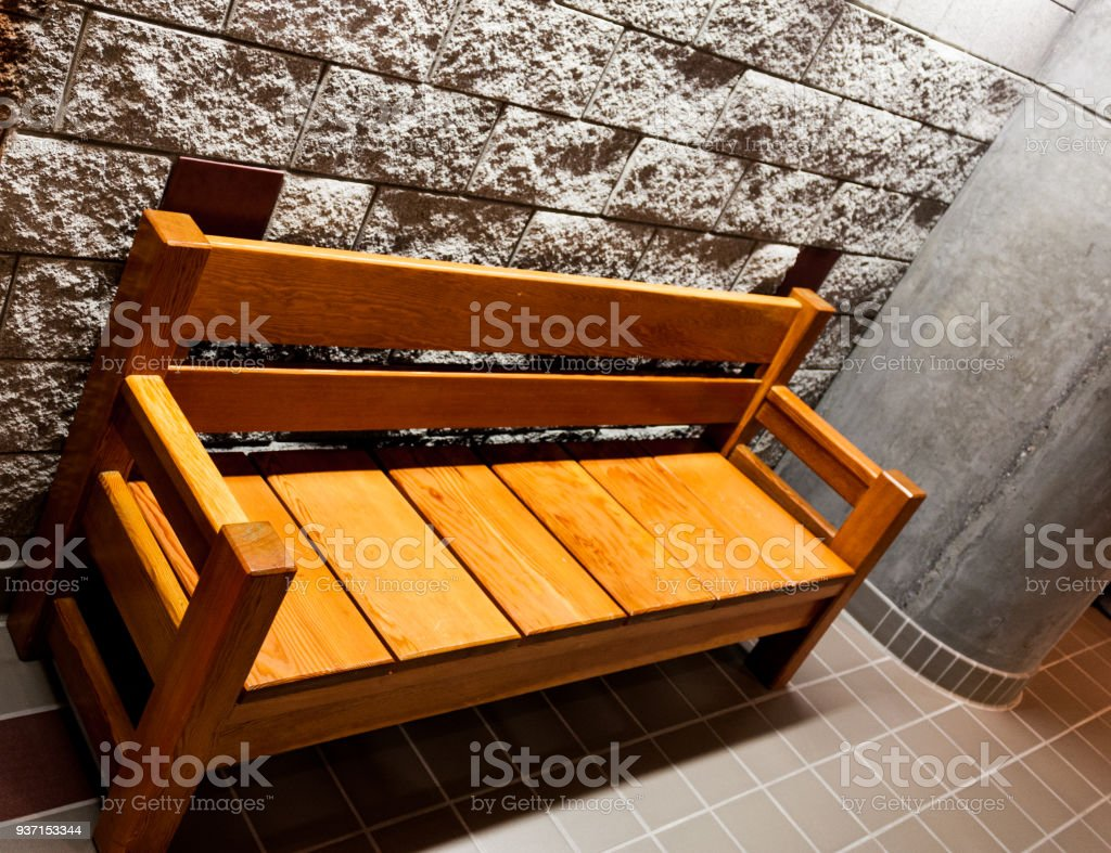 Sturdy wooden bench in front of a rough white stone wall next to a pillar stock photo