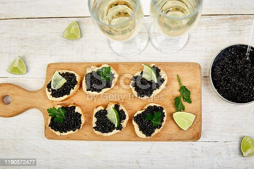 Sandwiches with black caviar. Sturgeon black caviar in wooden bowl, sandwiches and champagne on white background copy space. Top view.