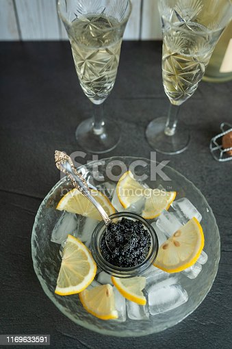 Sturgeon black caviar, sandwiches and champagne on on black background. View from above
