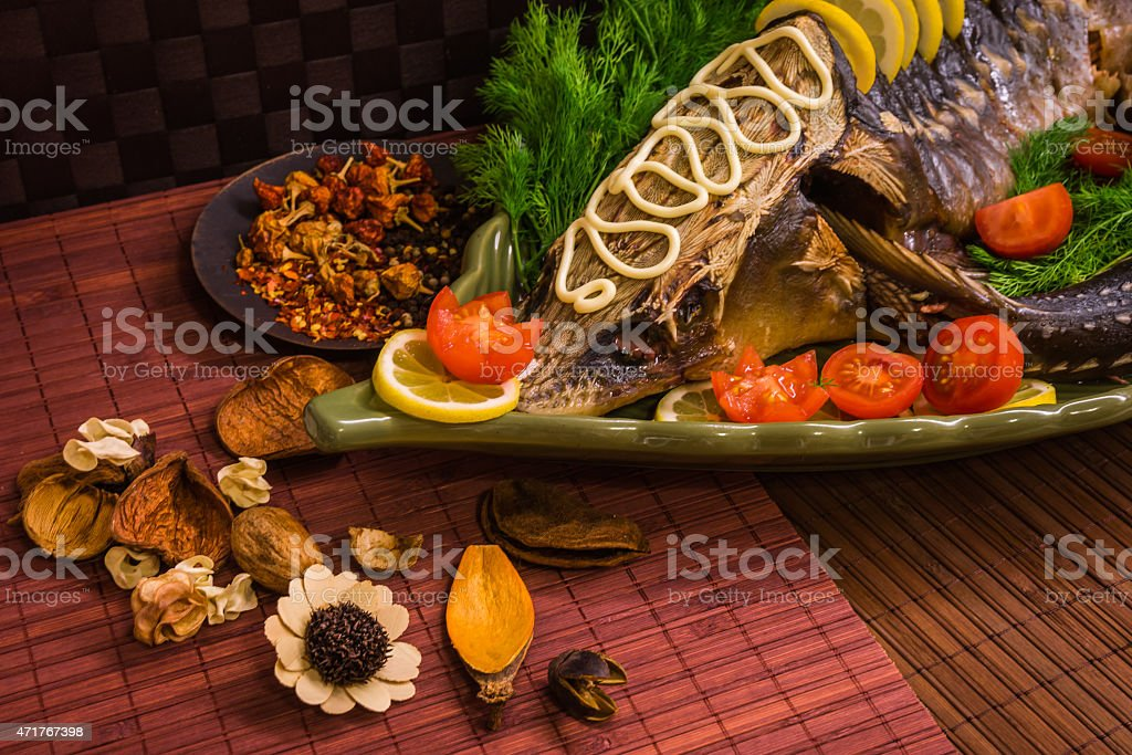 Sturgeon decorated with lemon and tomatoes on a green plate stock photo