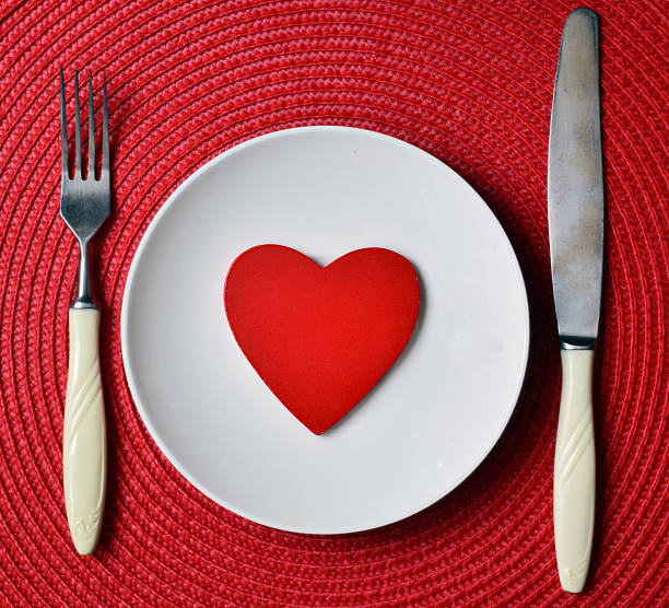 St.Valentine's Day romantic dinner concept. St.Valentine's Day romantic dinner concept with white plate, knife, fork and decorative wooden heart on red straw napkin background.Selective focus. table for two stock pictures, royalty-free photos & images