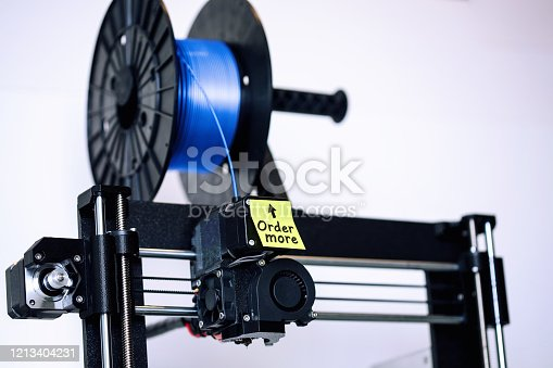 istock A FDM style 3d printer that has a spool of filament that is running low, and a sticky note as a reminder to order more silk PLA type of filament. 1213404231