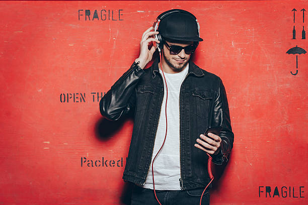 Style and music. Handsome young man adjusting his headphones and looking at his smart phone while standing against red background baseball cap stock pictures, royalty-free photos & images