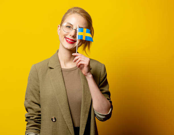 Style blonde woman in jacket with Swedish flag on yellow background stock photo