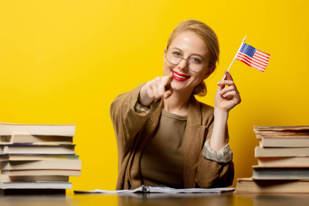 Style blonde woman sitting at table with books around and holds USA flag on yellow background stock photo