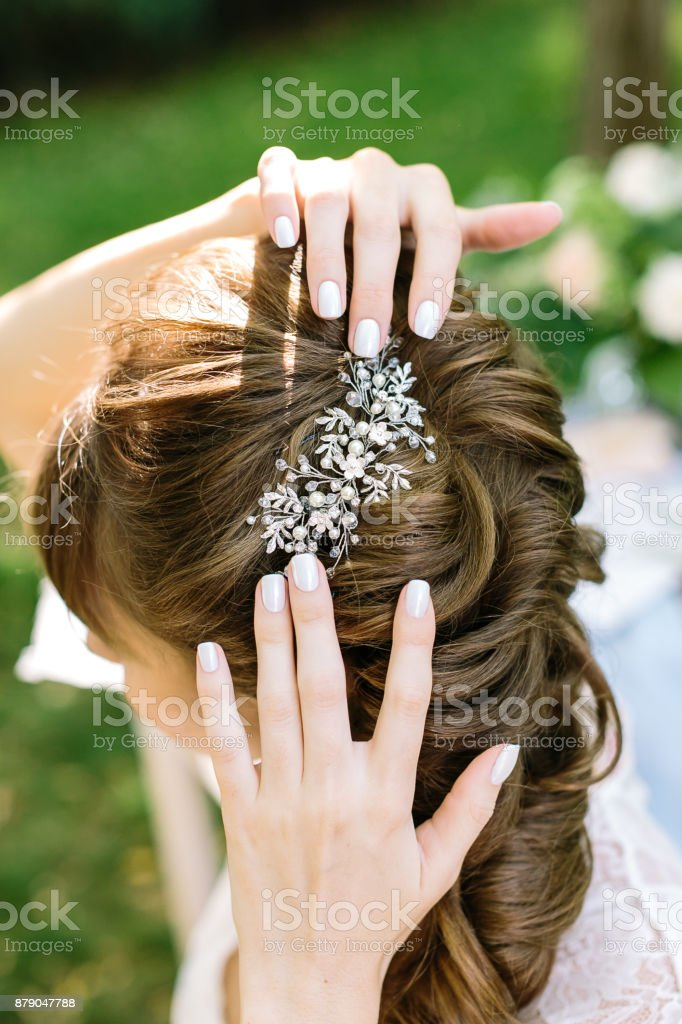 style, femininity, decoration concepr. in soft curly light brown hair of young woman there is shining barrette with diamonds in form of leaves and flowers stock photo