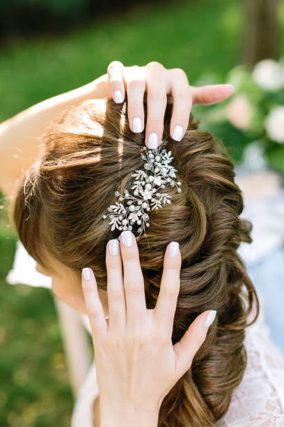 stil, weiblichkeit, dekoration concepr. in weichen lockige hellbraune haare jungen frau gibt es leuchtende haarspange mit diamanten in form von blättern und blüten - hochzeitsfrisur twilight stock-fotos und bilder