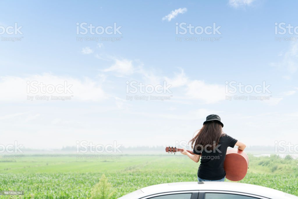 style girl sitting on car roof playing guitar against sky stock photo