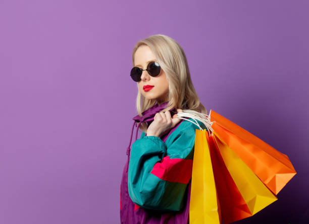 Style woman in 80s windbreaker and roud sunglasses hold shopping bags stock photo
