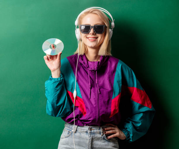 Style woman in 90s punk clothes with headphones and CD stock photo