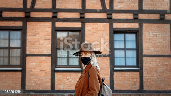 Style woman in hat and face mask with timber house on background
