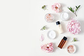 istock Styled beauty composition. Skin cream jar, tonicum bottle, roses, peony flower and Himalayan salt on white table background. Organic cosmetics, spa concept. Empty space, flat lay, top view. 1152020548