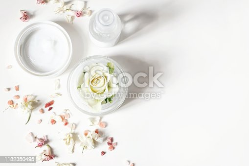 istock Styled beauty composition. Skin cream, shampoo bottle, dry flowers, rose and Himalayan salt. White table background. Organic cosmetics, spa concept. Empty space, flat lay, top view, web banner. 1132350495