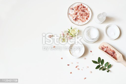 istock Styled beauty composition. Skin cream, tonicum bottle, dry flowers, rose and Himalayan salt on white table background. Organic cosmetics, spa concept. Empty space, flat lay, top view. 1125431708