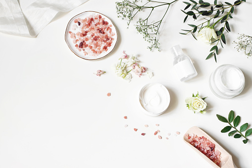 istock Styled beauty corner, web banner. Skin cream, tonicum bottle, dry flowers, leaves, rose and Himalayan salt. White table background. Organic cosmetics, spa concept. Empty space, flat lay, top view. 1132350479