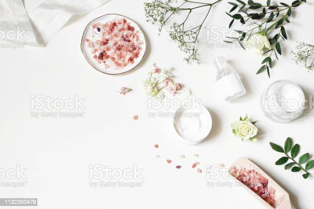 Photo of Styled beauty corner, web banner. Skin cream, tonicum bottle, dry flowers, leaves, rose and Himalayan salt. White table background. Organic cosmetics, spa concept. Empty space, flat lay, top view.