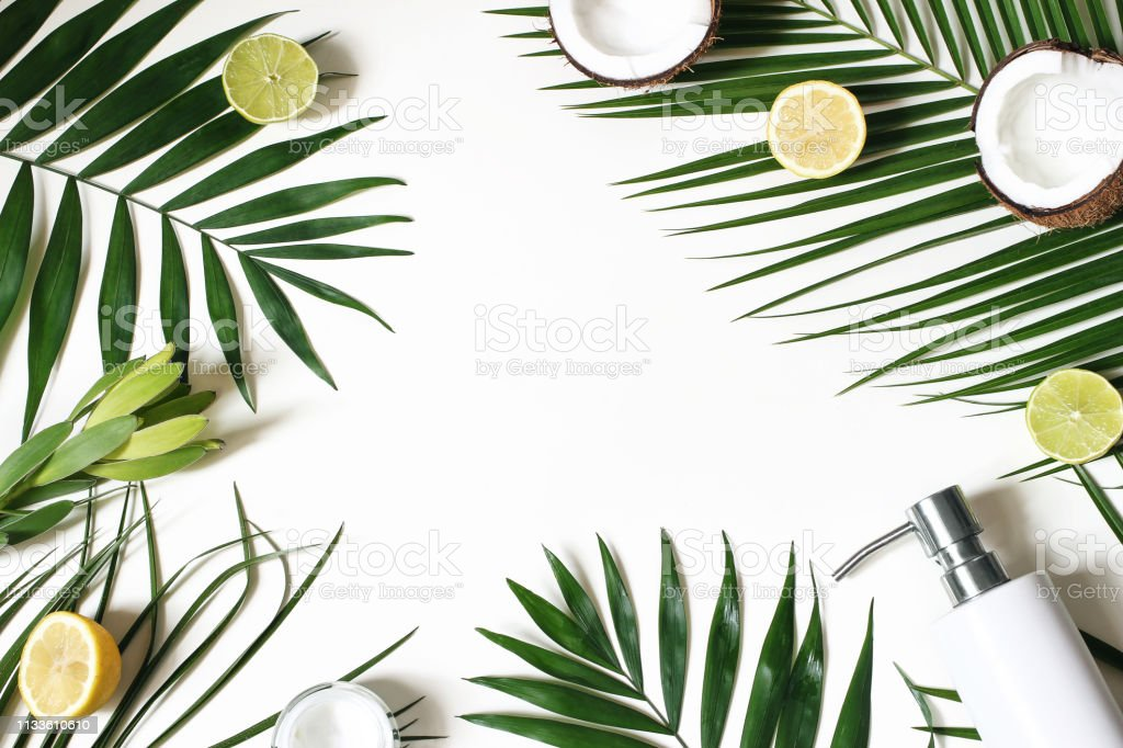 Styled beauty frame, web banner. Skin cream, soap bottle, coconut, lemons and lime fruit on lush palm leaves. White table background. Cosmetics, spa and tropical summer concept. Flat lay, top view. stock photo