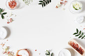 istock Styled beauty frame, web banner. Skin cream, tonicum bottle, dry flowers, leaves, rose and Himalayan salt. White table background. Organic cosmetics, spa concept. Empty space, flat lay, top view. 1125431744