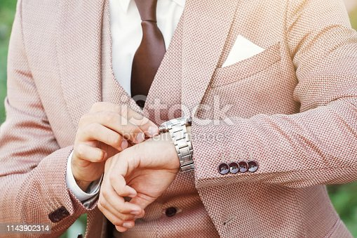 Styled man in vintage suit looking at his luxury wristwatch