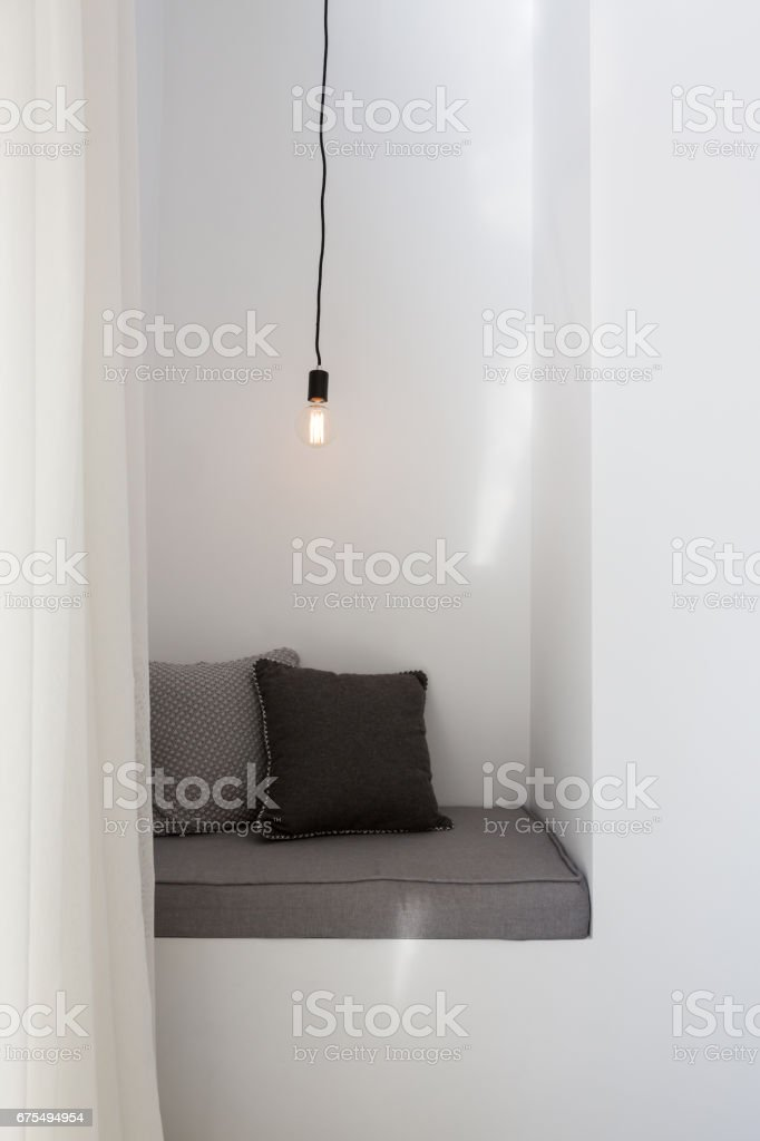 Styled reading nook with grey cushions and pendant light stock photo