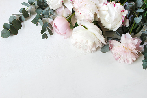 Styled stock photo. Decorative still life floral composition. Wedding or birthday bouquet of pink and white peony flowers and eucalyptus branches, white table background. Flat lay, top view.
