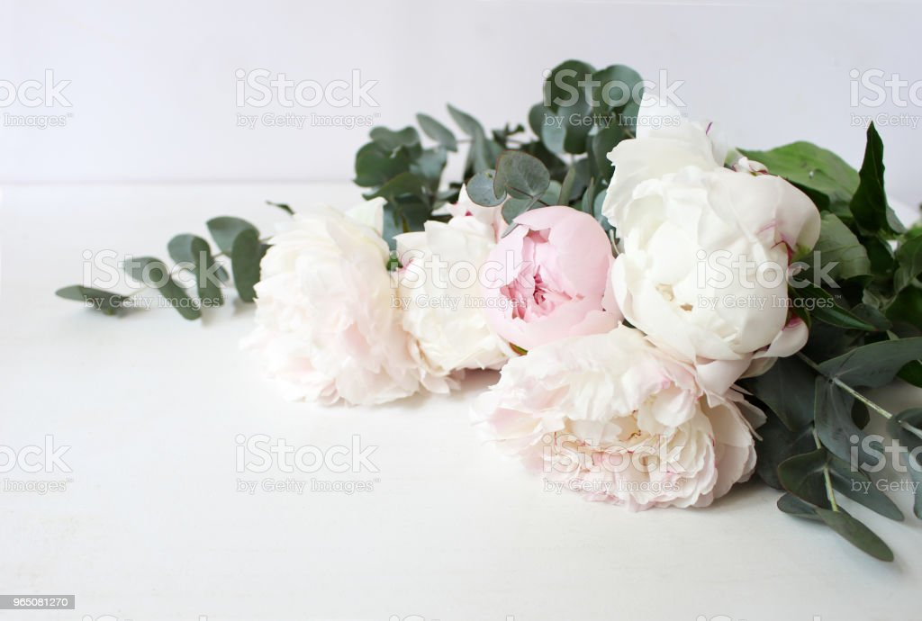 Styled stock photo. Decorative still life floral composition. Wedding or birthday bouquet of pink and white peony flowers and eucalyptus branches. White table background. royalty-free stock photo