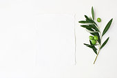 Styled stock photo. Feminine wedding desktop mockup scene with green olive branch and white empty vertical paper card. Foliage composition on white table background, top view. Flat lay picture.