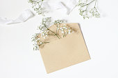 istock Styled stock photo. Feminine wedding desktop mockup with baby's breath Gypsophila flowers, satin ribbon and blank craft paper envelope mockup on white table background. Top view, flat lay. 1097461438