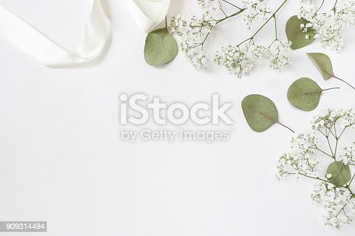 istock Styled stock photo. Feminine wedding desktop mockup with baby's breath Gypsophila flowers, dry green eucalyptus leaves, satin ribbon and white background. Empty space. Top view. Picture for blog 909314494