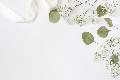 Styled stock photo. Feminine wedding desktop mockup with baby's breath Gypsophila flowers, dry green eucalyptus leaves, satin ribbon and white background. Empty space. Top view. Picture for blog