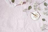 istock Styled stock photo. Feminine wedding desktop scene. Baby's breath Gypsophila flowers, dry green eucalyptus leaves, satin ribbon, golden scissors on pink linen background. Empty space. Top view. 1128871242