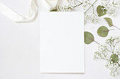 istock Styled stock photo. Feminine wedding desktop stationery mockup with blank greeting card, baby's breath Gypsophila flowers, dry green eucalyptus leaves, satin ribbon and white background. Empty space. Top view. Picture for blog. 944314068