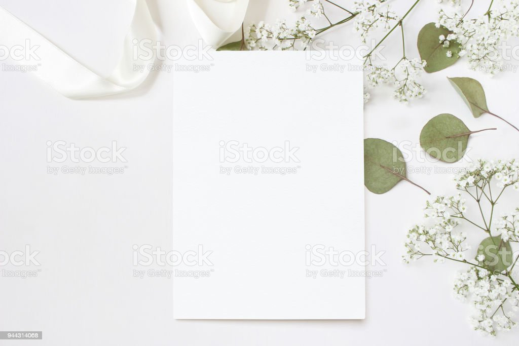 Styled stock photo. Feminine wedding desktop stationery mockup with blank greeting card, baby's breath Gypsophila flowers, dry green eucalyptus leaves, satin ribbon and white background. Empty space. Top view. Picture for blog. stock photo