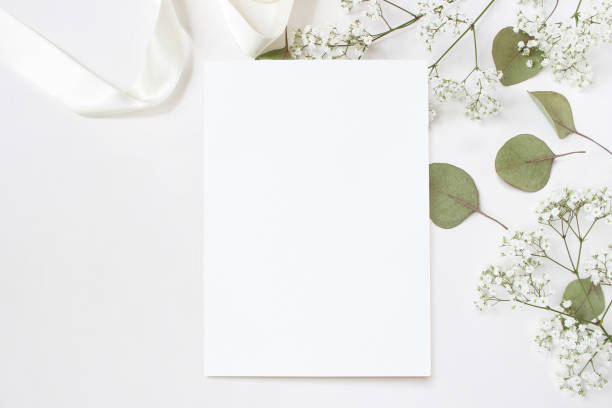 styled stock photo. feminine wedding desktop stationery mockup with blank greeting card, baby's breath gypsophila flowers, dry green eucalyptus leaves, satin ribbon and white background. empty space. top view. picture for blog. - приглашение стоковые фото и изображения