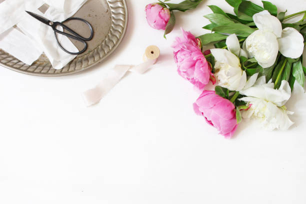 Styled stock photo. Feminine wedding or birthday table composition with floral bouquet. White and pink peonies flowers, old vintage scissors, silver tray and silk ribbons. White background. stock photo