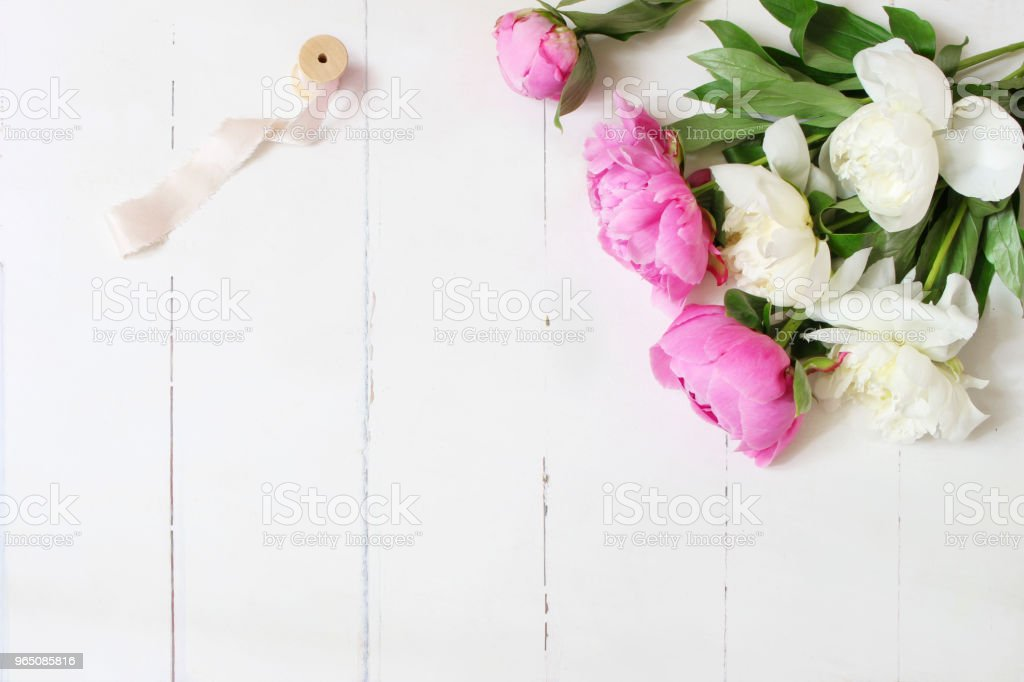 Styled stock photo. Feminine wedding or birthday table composition with floral bouquet. White and pink peonies flowers and spool of silk ribbon. White wooden background. Flat lay, top view. royalty-free stock photo