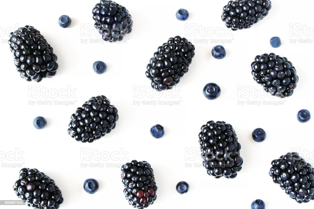 Styled stock photo. Summer healthy fruit composition with juicy blackberries and blueberries isolated on white table background. Food pattern. Empty space. Closeup Flat lay, top view. stock photo