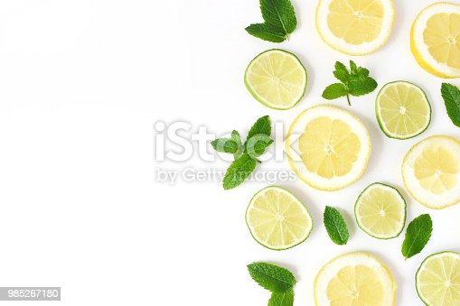 Styled stock photo. Summer herbs and fruit composition. Lime, lemon slices and fresh green mint leaves isolated on white table background. Juicy food pattern, empty space. Flat lay, top view.