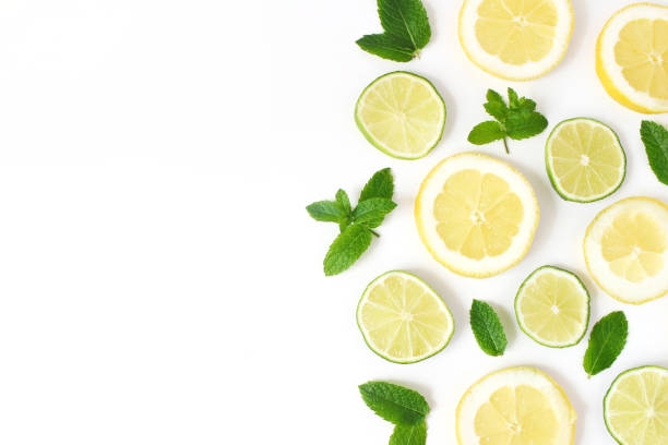 Styled stock photo. Summer herbs and fruit composition. Lime, lemon slices and fresh green mint leaves isolated on white table background. Juicy food pattern. Empty space. Flat lay, top view. stock photo
