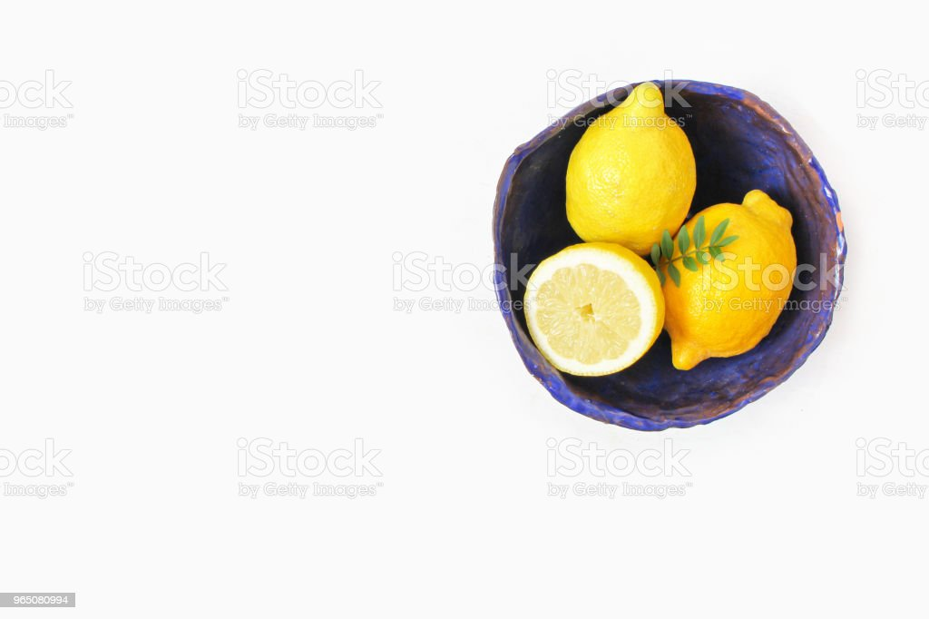 Styled stock photo. Yellow lemon fruit in decorative handmade cobalt blue ceramic bowl. Still life floral composition. White table background. Flat lay, top view. royalty-free stock photo