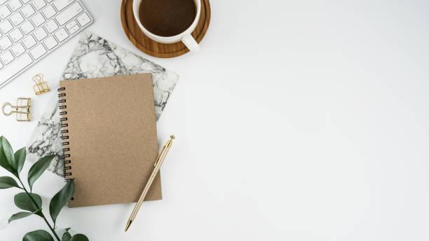 tavolo da tavolo da ufficio bianco per la fotografia di repertorio con notebook, computer, forniture e tazza di caffè in stile stock. vista dall'alto con spazio di copia. lay piatto. - flat lay foto e immagini stock